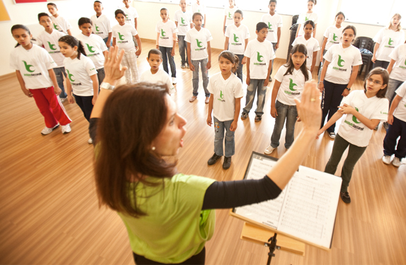 Photo taken above a woman's head looking from the front. She is conducting a chorus of children of various ages
