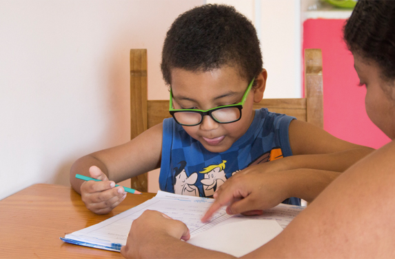 Photo of an 8-year-old boy, wearing glasses, writing on a piece of paper. A woman points out letters in a notebook.