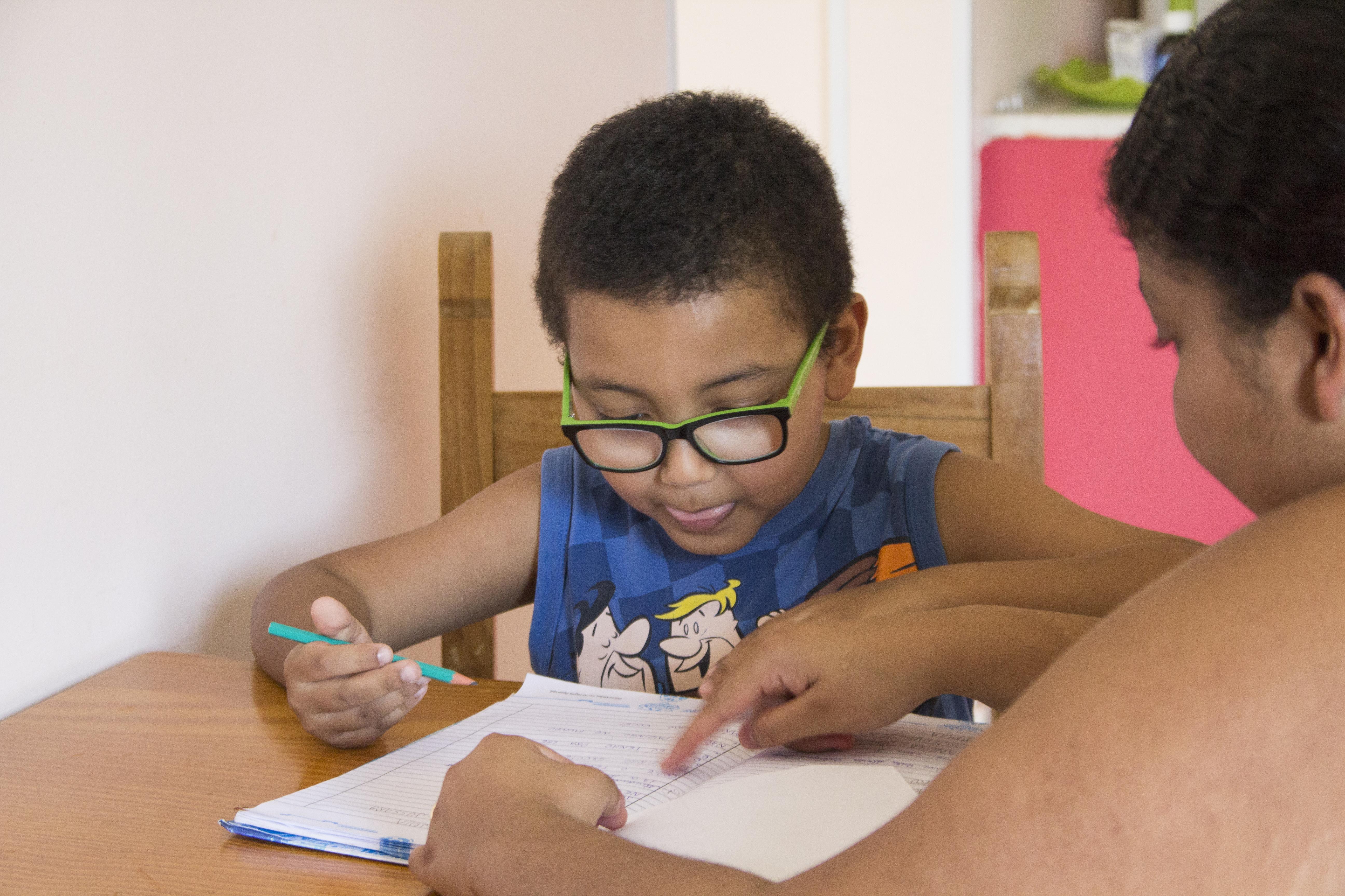 Foto de um menino de 8 anos, com óculos, escrevendo e uma folha. Uma mulher indica letras em um caderno