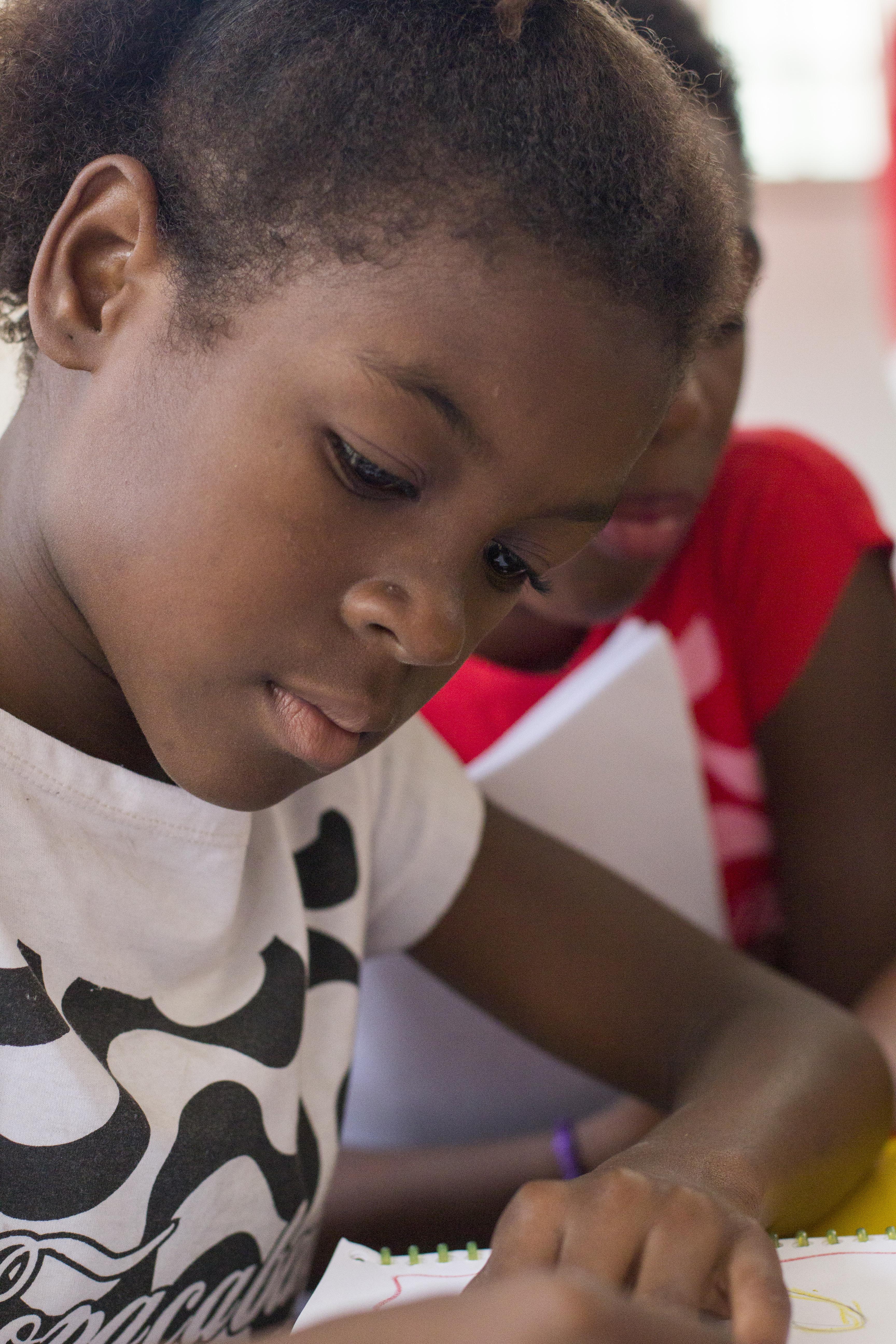 Foto de uma menina negra, de 9 anos, escrevendo em um caderno
