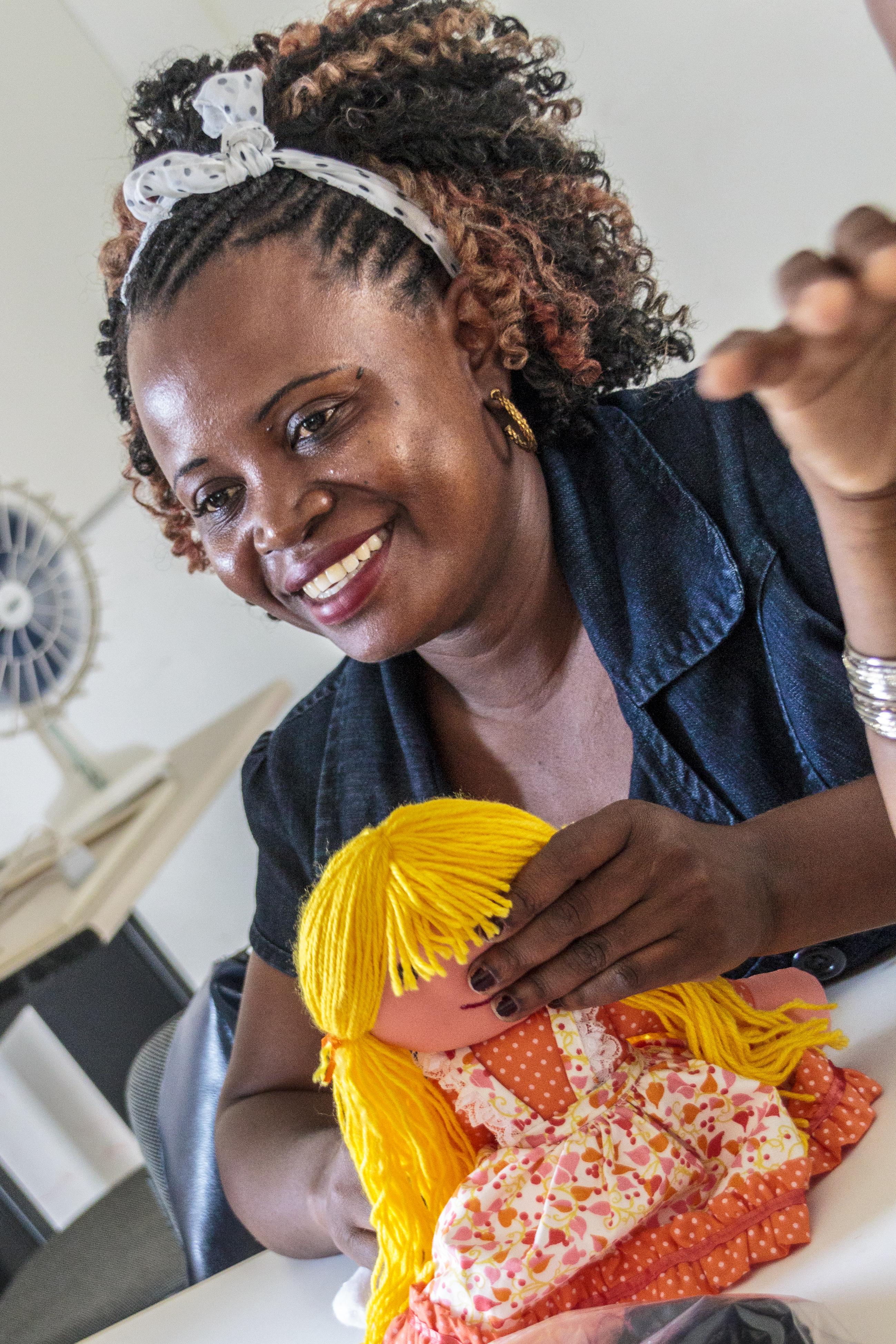 Foto de uma mulher negra, com cabelos crespos e longos presos por uma faixa branca. Ela está segurando uma boneca de pano e sorri