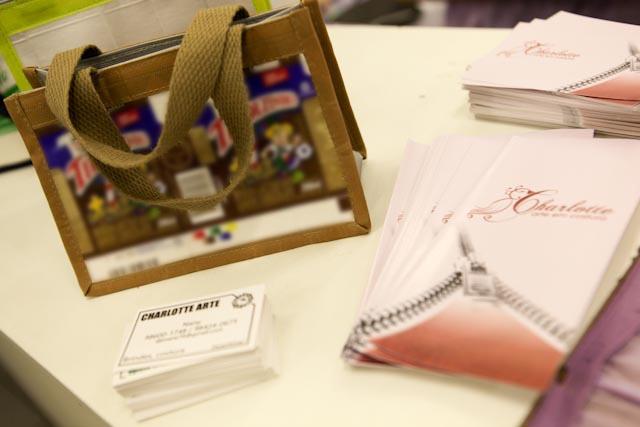 Foto em close de uma pequena sacola feita com caixas de Toddynho. Ao lado, em uma superfície, há cartões e panfletos