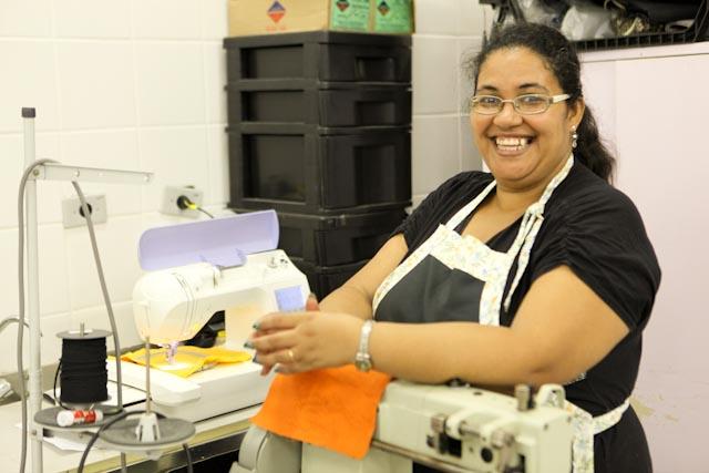 Foto de uma mulher apoiada em uma máquina de costura. Ela posa para a foto e sorri.