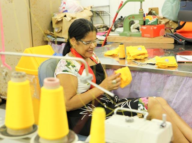 Foto de uma costureira sentada. Ela segura um pano amarelo e está sentada ao lado de uma bancada.