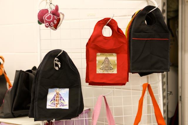Foto de bolsas pretas e vermelhas penduradas em um suporte de ferro. Na frente das bolsas, há a imagem de uma santa.