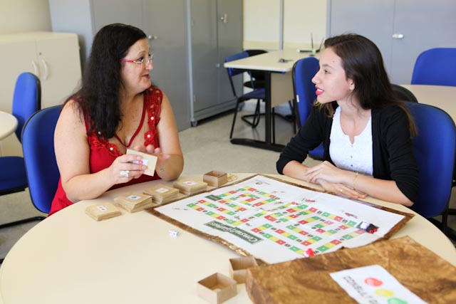 Foto de duas mulheres ao redor de uma mesa. Sobre a mesa há um cronograma.