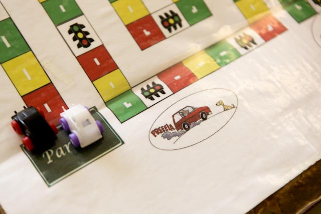 """Foto de parte de um jogo de tabuleiro. No local escrito """"partida"""", há dois carrinhos de plástico."""