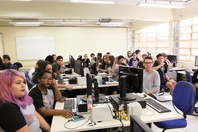 Foto de uma sala de informática com vários jovens em frente a computadores.