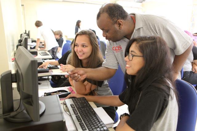 Foto de duas adolescentes recebendo orientações de um professor durante uma aula de informática.