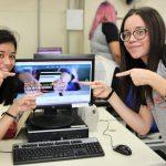 Foto de duas jovens apontando para a tela de um computador e sorrindo