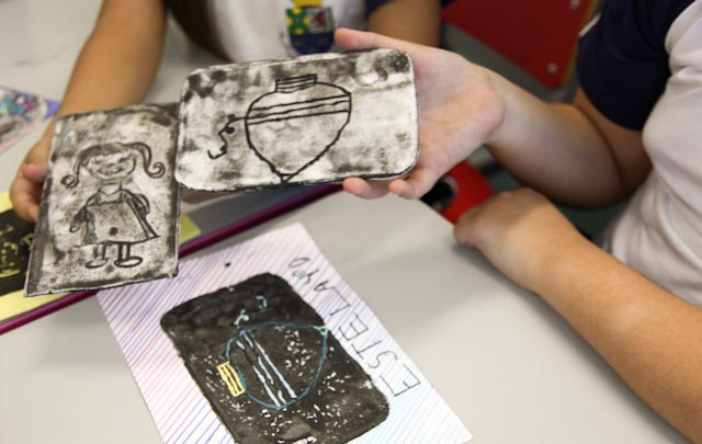 Foto de duas matrizes de stêncil feitas com gesso. Em uma delas há uma garotinha e na outra há um pião.