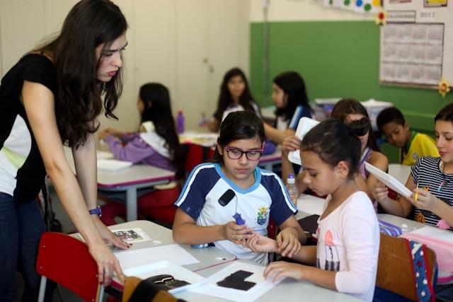 Foto de uma professora dando instruções para duas alunas durante uma atividade de artes na sala de aula.