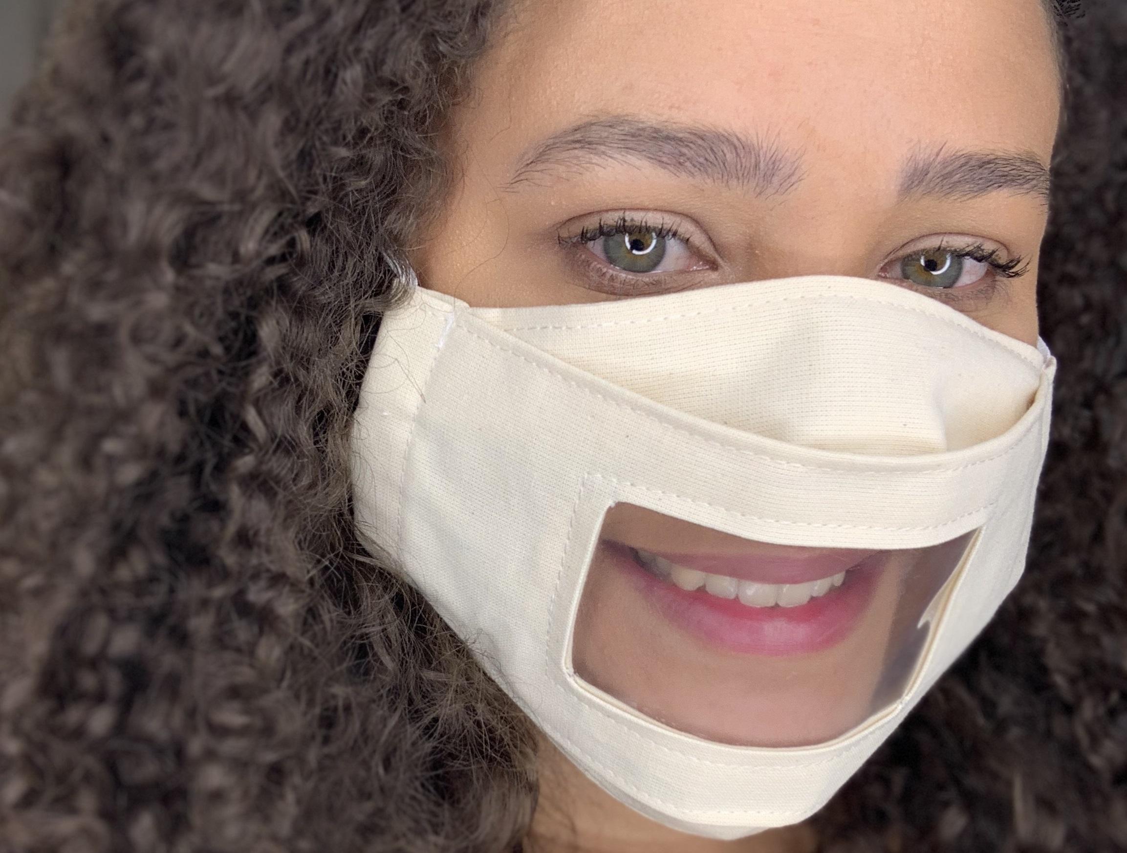 Foto de uma mulher jovem usando uma máscara de pano com visor transparente na região da boca.