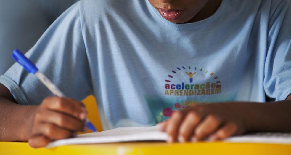 Foto do dorso de um garoto. Ele está com os braços sobre a carteira escolar, segurando uma caneta azul.