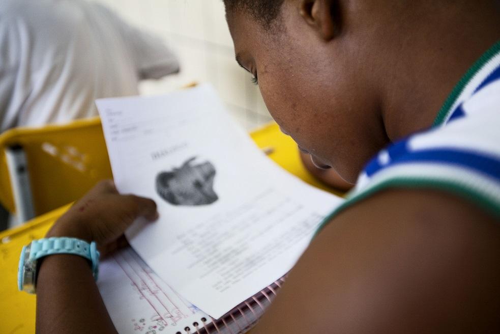 Foto da lateral do rosto de uma criança lendo um papel durante a aula.