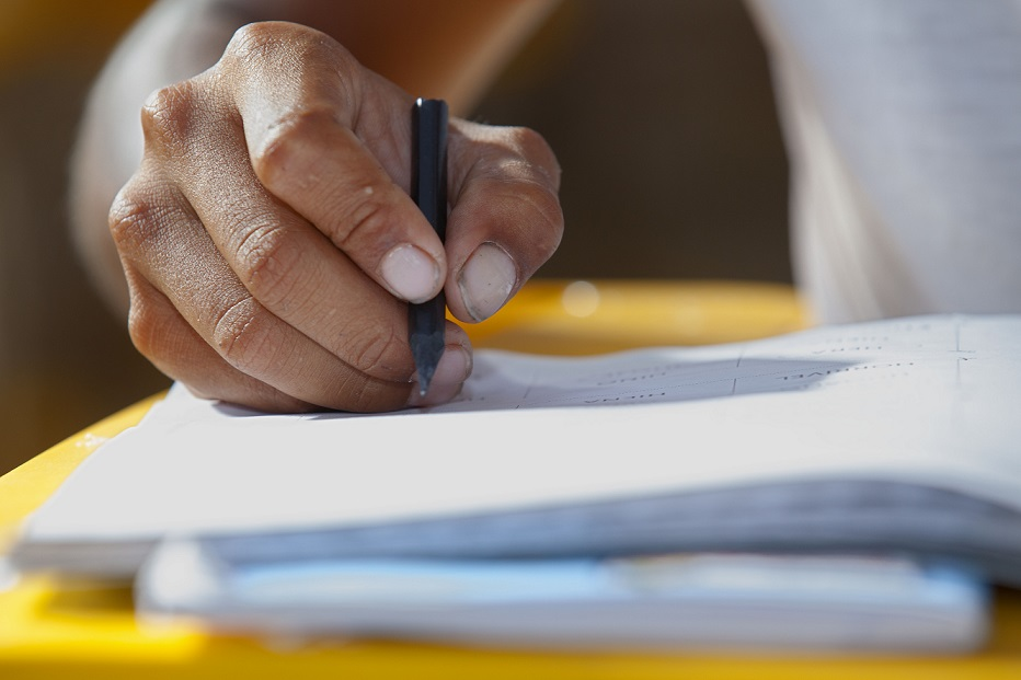 Foto de uma mão segurando um lápis pequeno sobre um caderno.