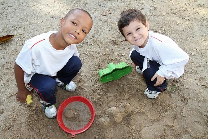 Foto de dois garotos pequenos brincando em uma caixa de areia na escola.