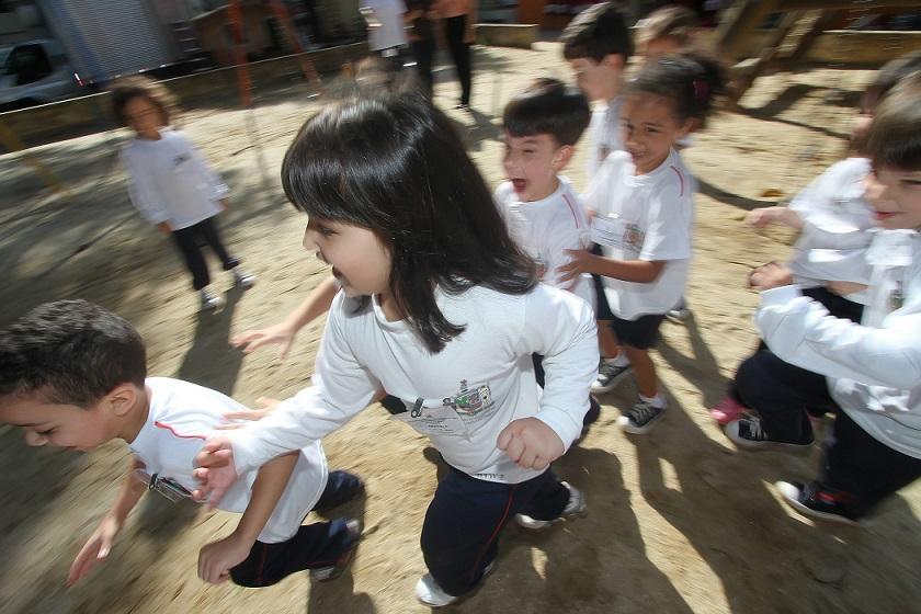 Foto de crianças brincando em uma caixa de areia na escola.