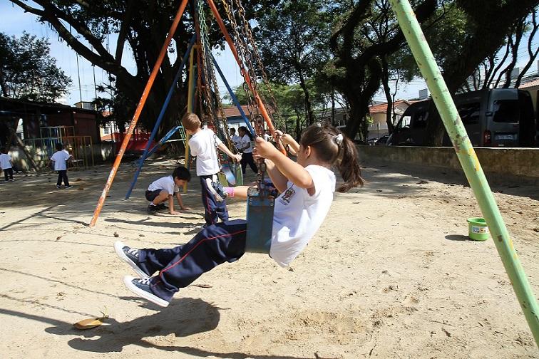 Foto de uma garota vista de lado brincando em uma balança na escola.
