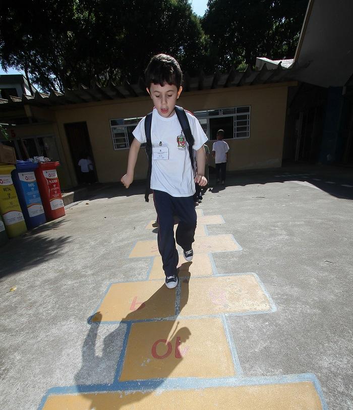 Foto de um menino andando em cima de uma pintura no chão da brincadeira amarelinha. Ele está com uniforme escolar e mochila nas costas.