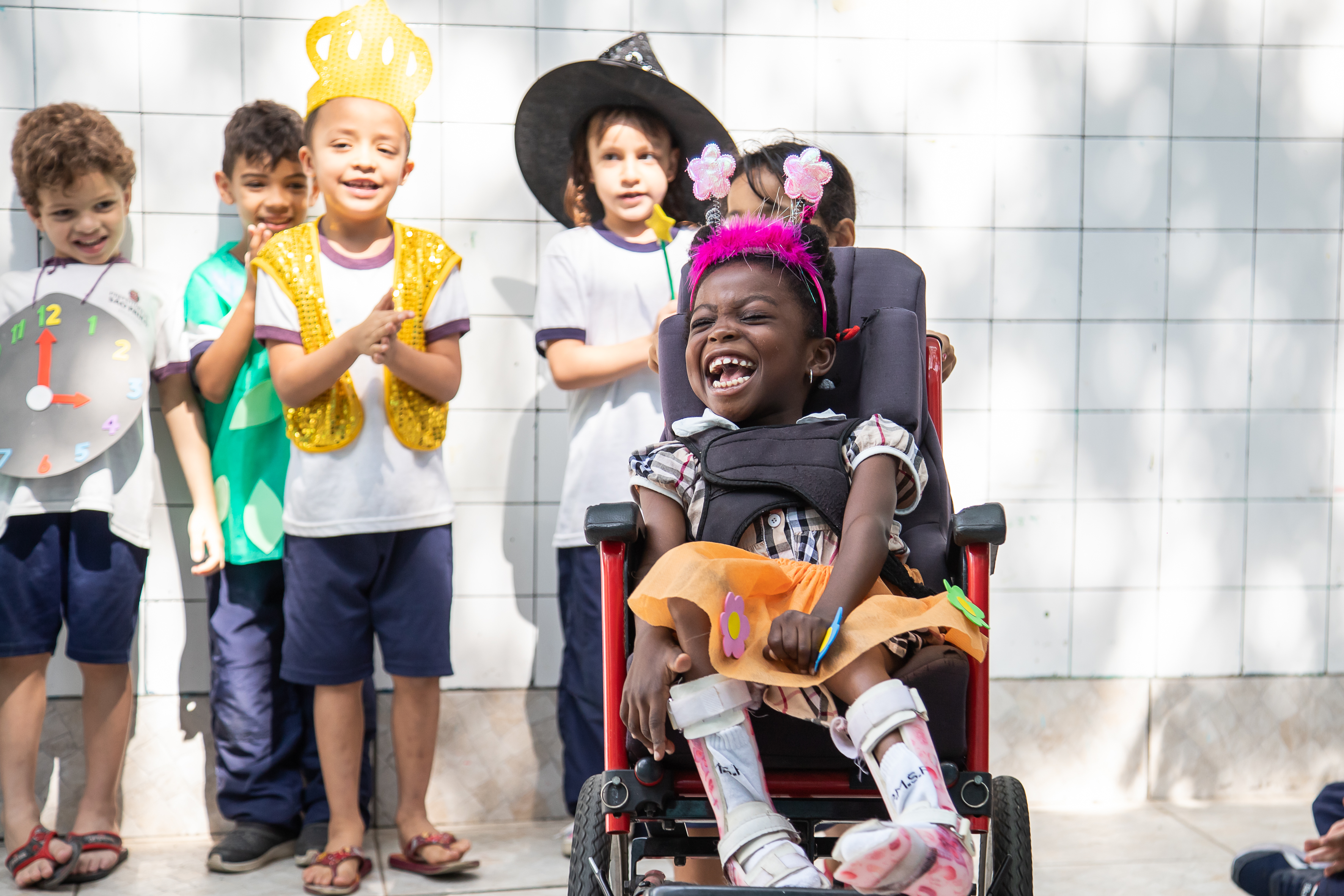 Foto de um grupo diverso de crianças fantasiadas. Uma delas está em uma cadeira de rodas.