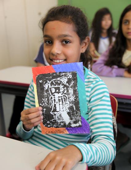 Foto de uma garota segurando um papel com ilustração feita em técnica em stêncil.