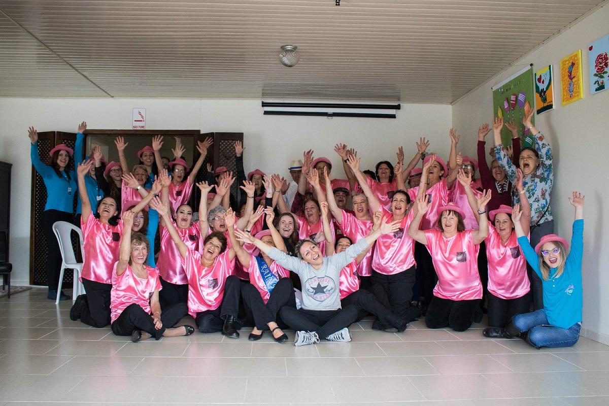Foto de um grupo de pessoas com roupas, em sua maioria, na cor rosa, com as mãos para cima. Elas estão sorrindo.