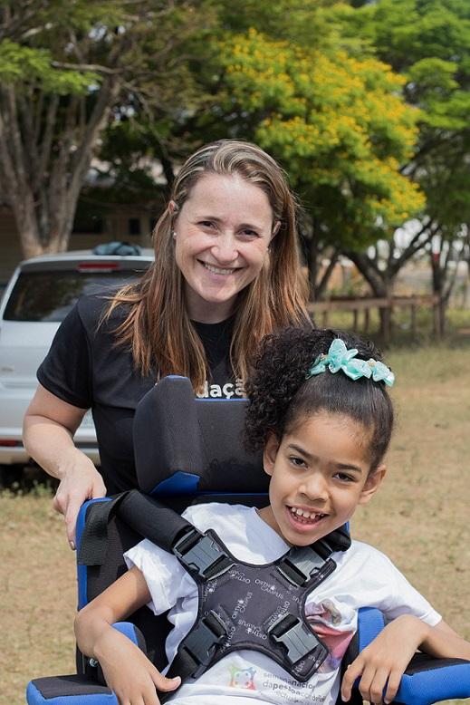 Foto de uma mulher em pé sorrindo atrás de uma menina em uma cadeira de rodas.