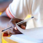 Foto de uma mão segurando uma caneta e folheado um caderno