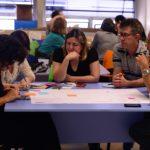 Foto de um grupo de pessoas, com homens e mulheres, sentados e escrevendo em um cartaz sobre uma mesa