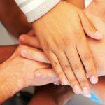 Foto de diversas mãos sobrepostas, como em um grito de guerra em equipe