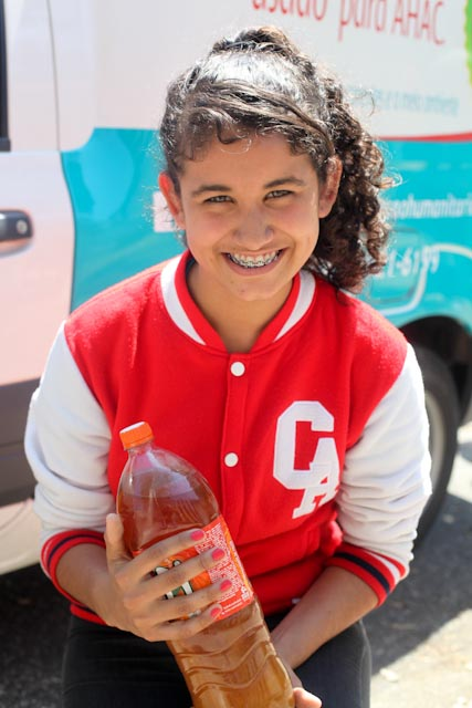 Foto de uma menina sorrindo, segurando uma garrafa PET com óleo. Ela é morena e está com os cabelos presos.