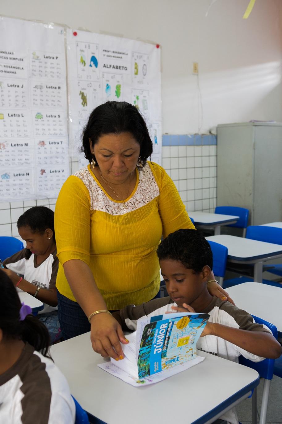 Foto de uma senhora em pé ao lado de um menino que está sentado em uma sala de aula. Ela está folheando um livro e apoiando uma das mãos nas costas da criança. Os dois olham para o livro.