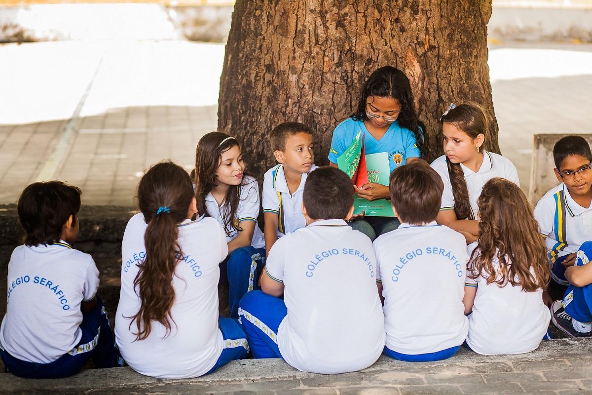 Foto de uma mulher sentada mostrando um livro para crianças uniformizadas. Ela está com as costas apoiada em um grande tronco de árvore e as crianças olham para o livro.
