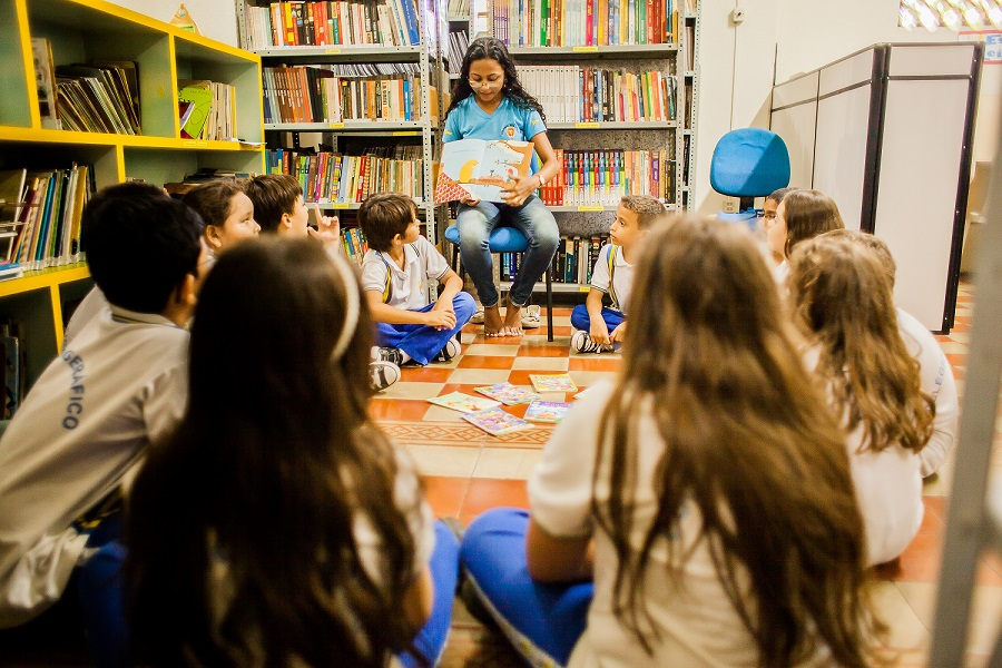 Foto de uma sala cheia de livros com diversas crianças sentadas em círculo olhando para uma mulher sentada em uma cadeira mostrando um livro.