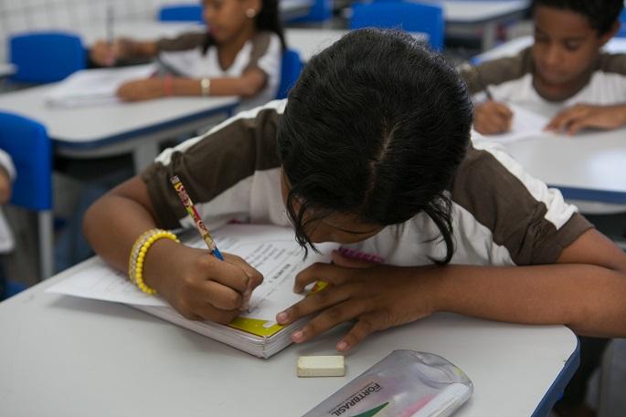 Foto de criança sentada escrevendo em uma folha de papel. Ela está com os dois braços apoiados na mesa. Ao fundo, há crianças sentadas.