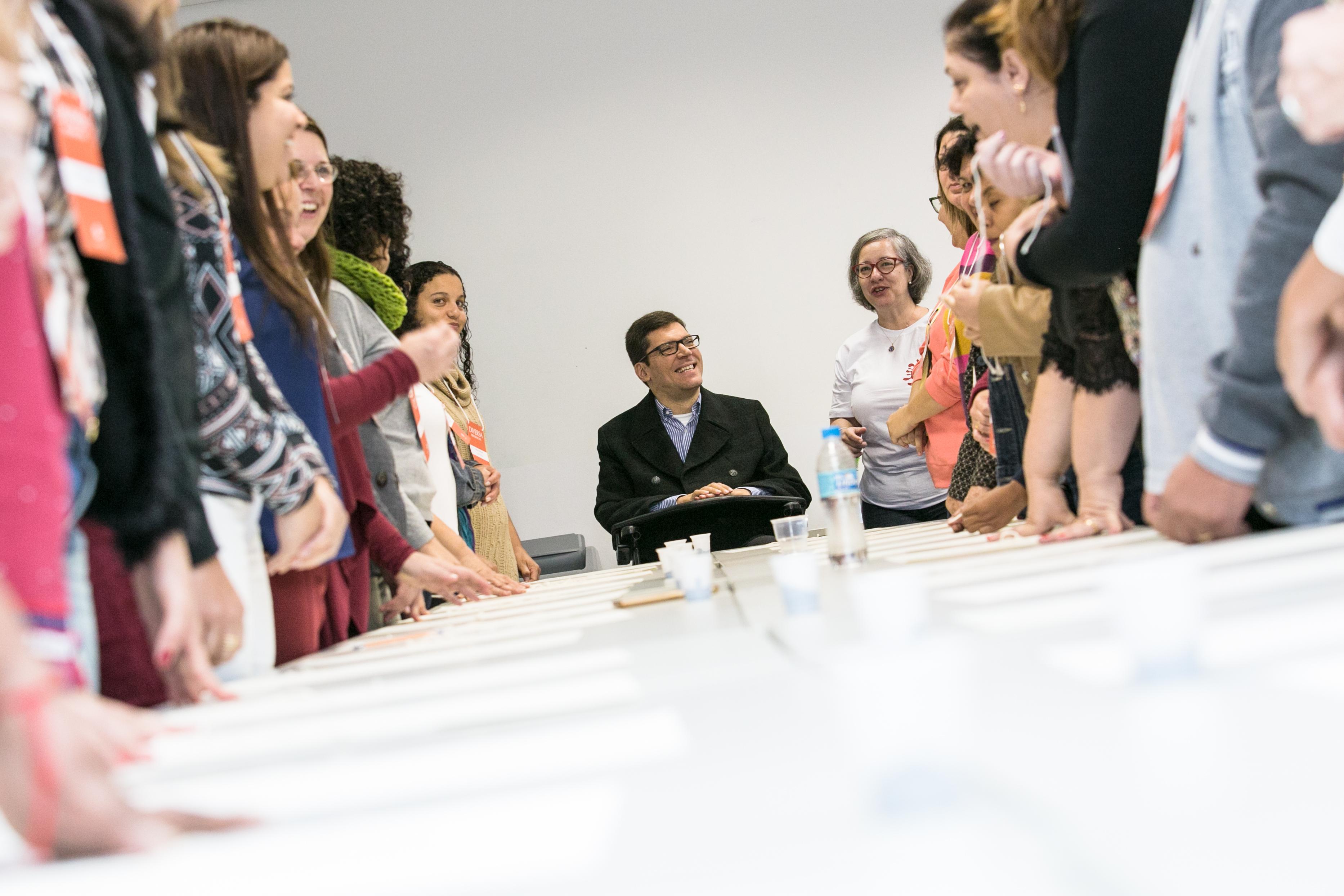Foto do Rodrigo Mendes na ponta de uma mesa grande retangular. Ele está na cadeira de rodas sorrindo e olhando para o lado. Há pessoas em pé sorrindo e olhando para ele nos dois lados da mesa.