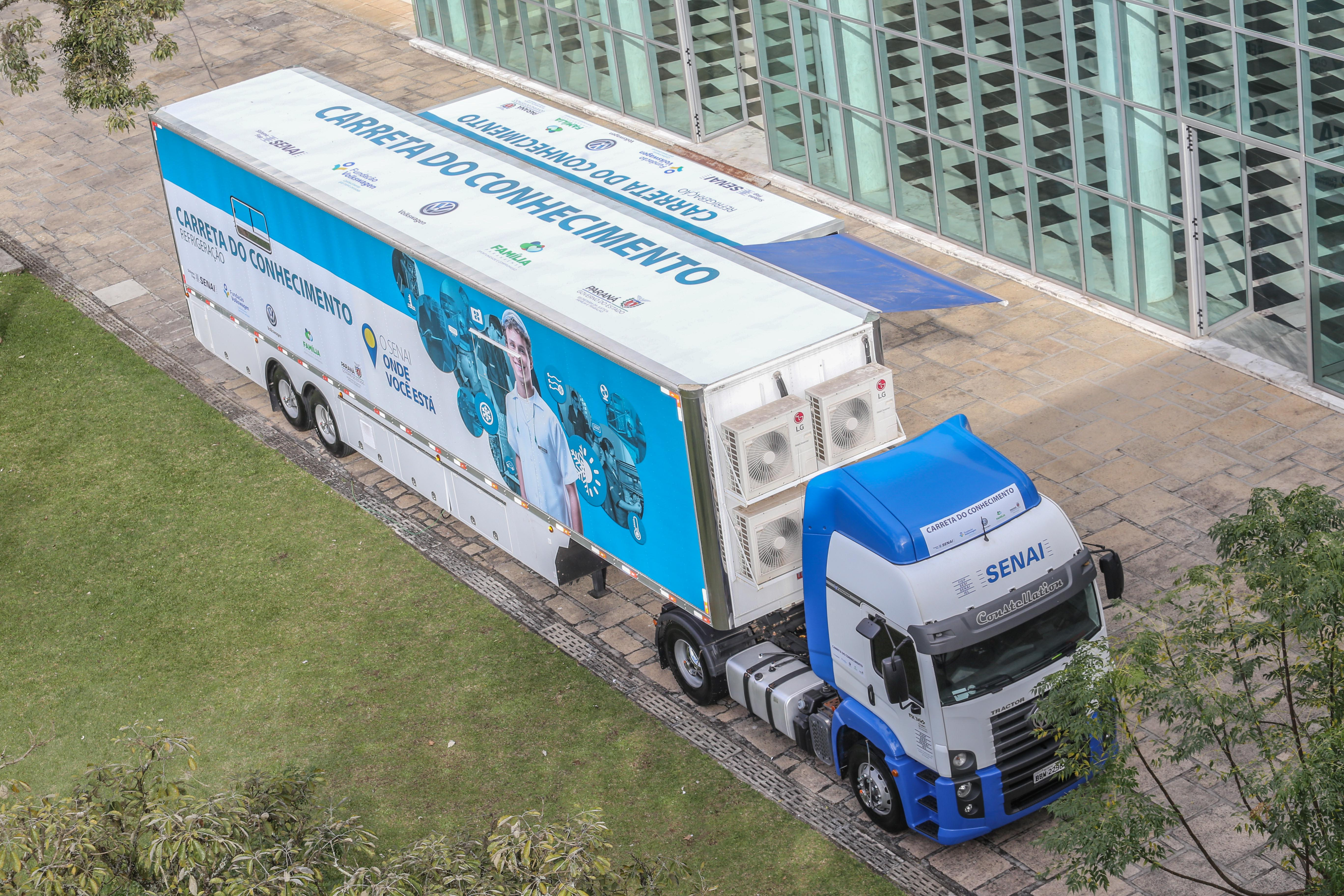 Foto de um caminhão visto de cima. Ele está estacionado em um pátio ao lado de um prédio.