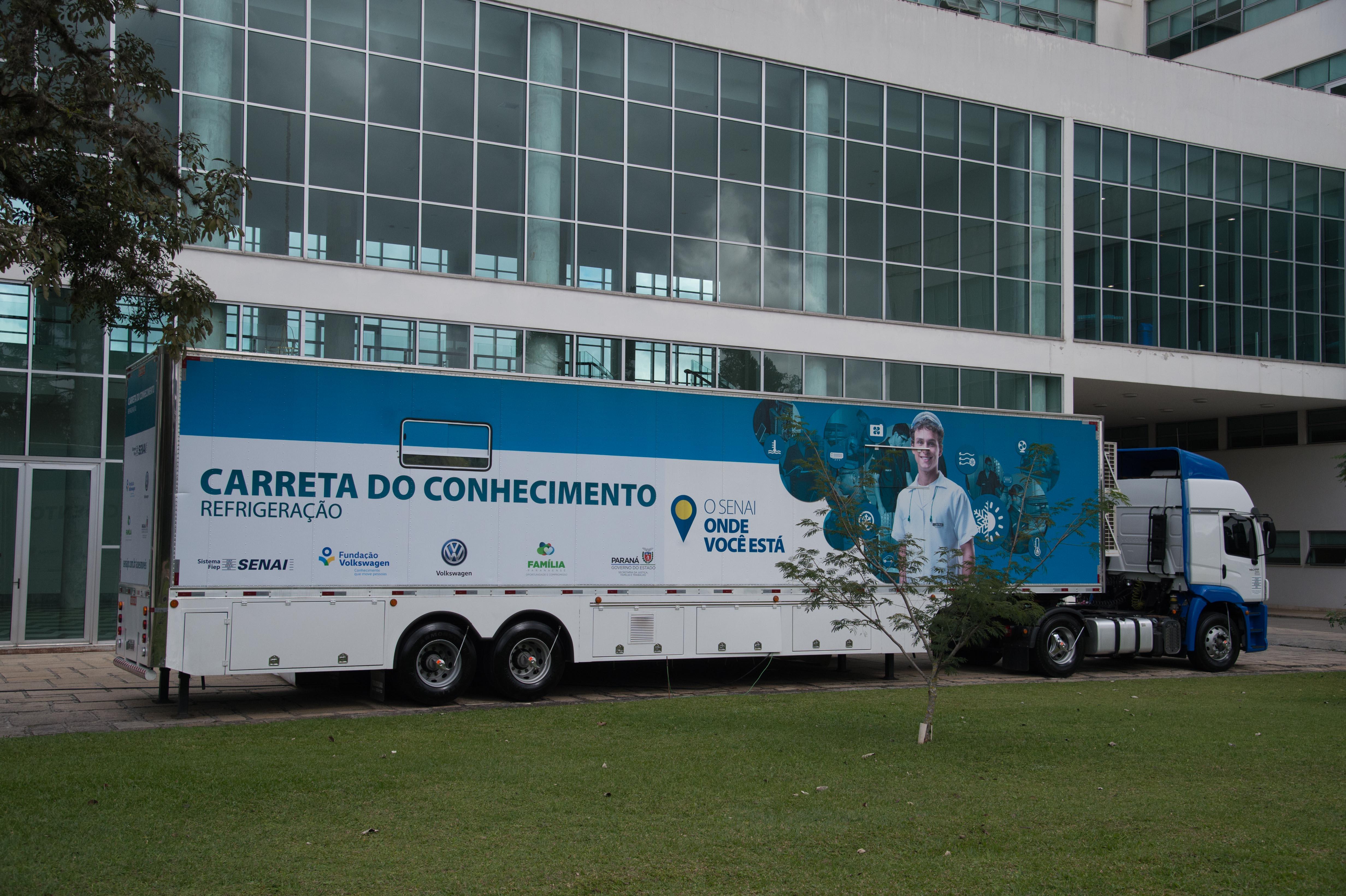 Foto de um caminhão com a sua carreta plotada com o texto Carreta do Conhecimento refrigeração.