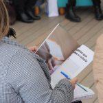 Foto em close de uma mulher segurando um material gráfico.
