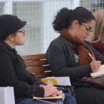 Foto de uma mulher fazendo anotação em um caderno. Ao seu lado, há duas mulheres.