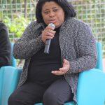 Foto de uma mulher negra falando ao microfone
