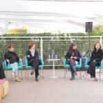Foto de uma mulher negra falando ao microfone com outras pessoas ao seu redor sentadas em círculo