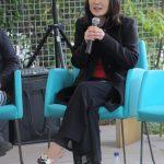 Foto de uma mulher sentada falando ao microfone