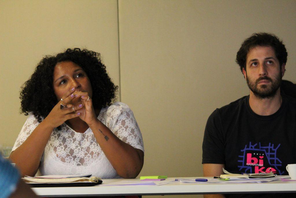 Foto de uma mulher e um homem sentados à mesa olhando com atenção em uma mesma direção