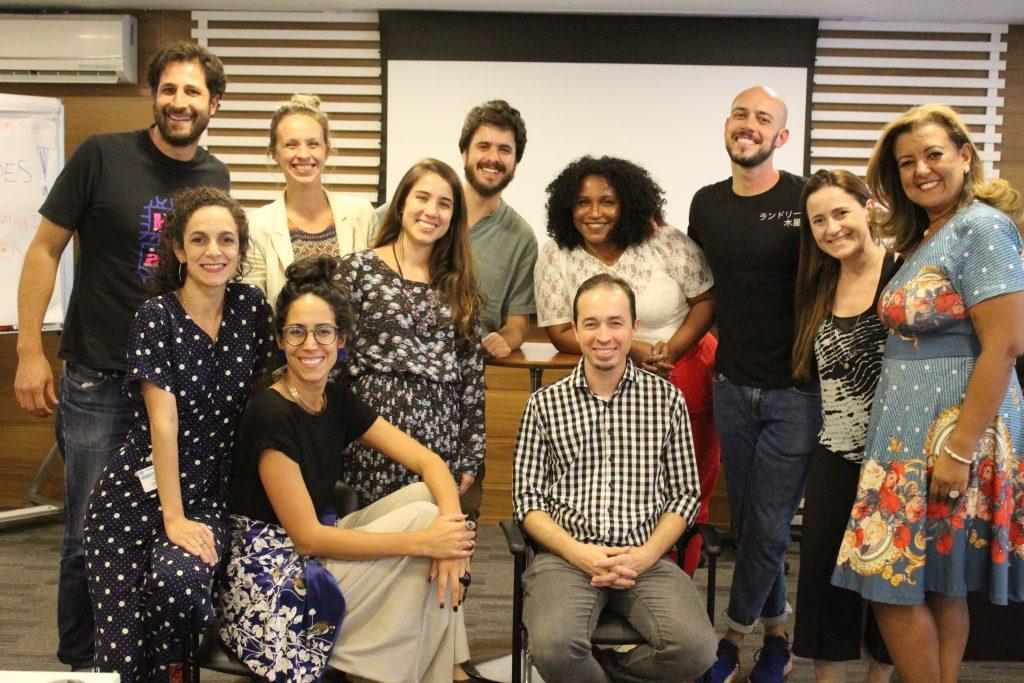 Foto de um grupo de onze adultos sorrindo para a câmera