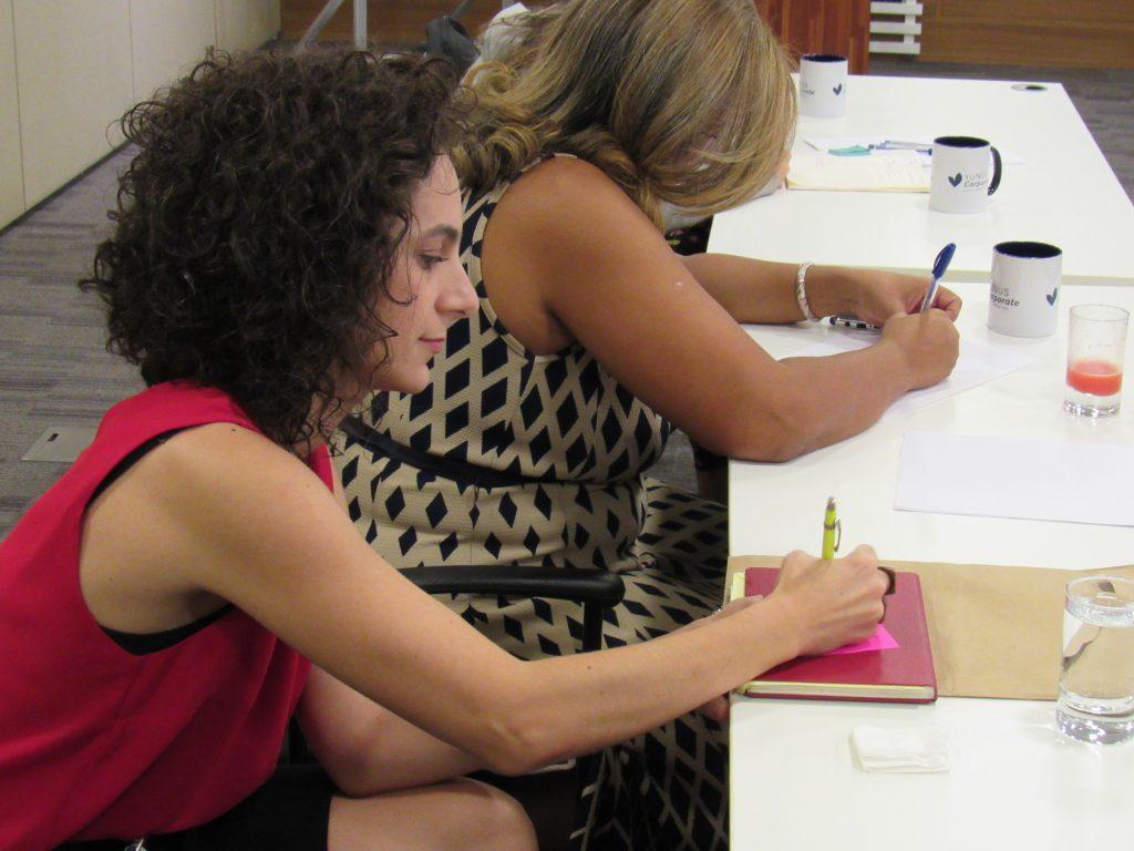 Foto de duas mulheres sentadas escrevendo em um papel