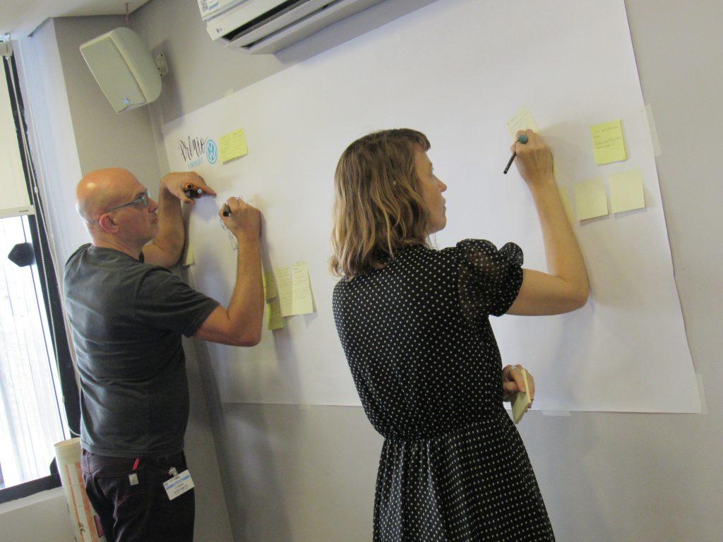 Foto de um homem e uma mulher em pé escrevendo em uma grande folha branca presa à parede
