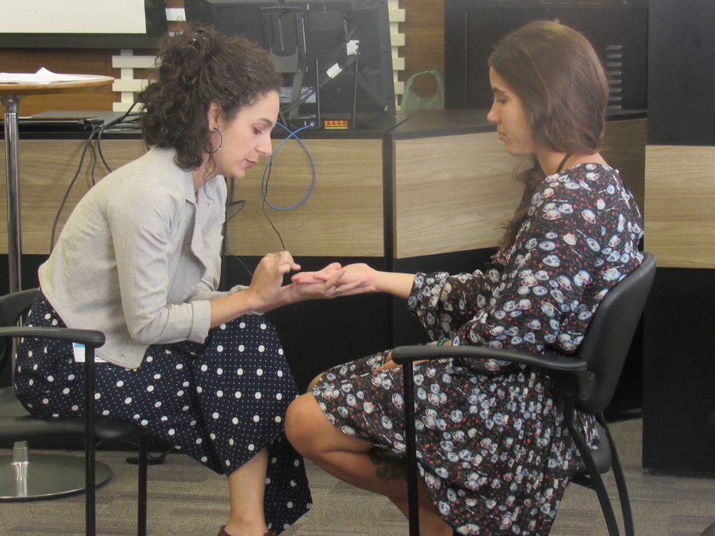 Foto de duas mulheres sentadas uma de frente para a outra