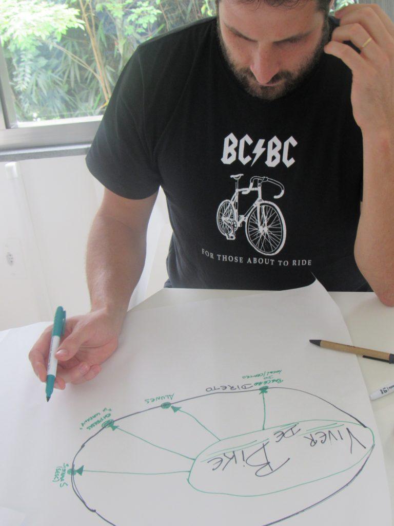Foto de um homem com uma caneta na mão olhando para um cartaz em cima da mesa.